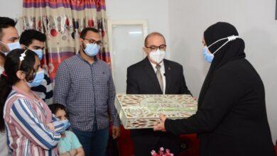 صورة رئيس جامعة أسيوط يسلم أسر شهداء الأطقم الطبية هدايا مقدمة من الرئيس السيسى